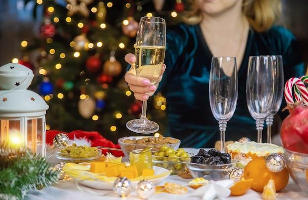 Champagne in mano su un albero di natale da solo