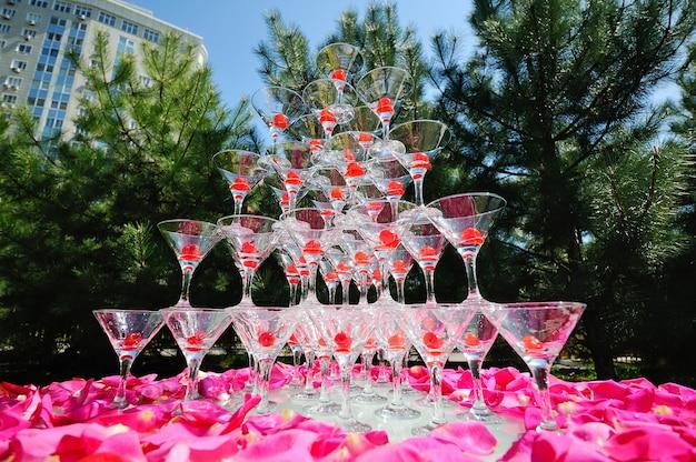 Diapositiva di champagne su uno sfondo di petali di rosa rosa e verdi
