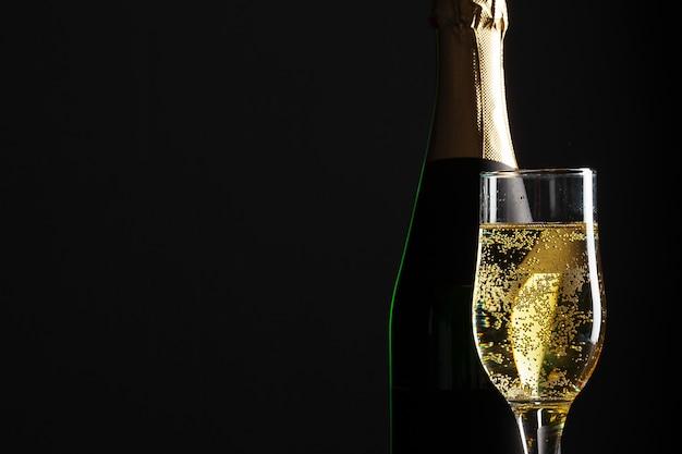 Vetro e bottiglia di vino di champagne sul nero