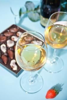 Champagne o vino in bicchieri e scatola di cioccolatini.