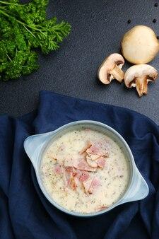Zuppa di crema di funghi prataioli con pancetta e ingredienti sul tavolo vista. crea soupe su un tavolo in tessuto e cemento scuro.