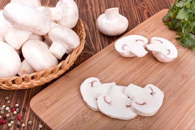Funghi prataioli su un tagliere su un fondo di legno