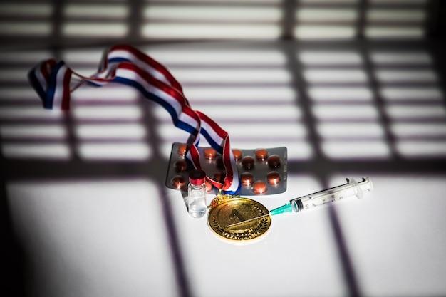 Medaglia d'oro campione, siringa di sostanza dopante, compressa di pillole e fiala di sostanza proibita con luci e ombre di una tenda che entra dalla finestra. sport e concetto di doping