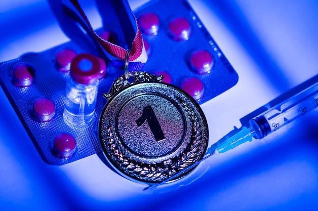 Medaglia d'oro campione, siringa con sostanza dopante, compressa di pillole e fiala con sostanza proibita con luci e ombre di una tenda che entra dalla finestra di notte. sport e concetto di doping