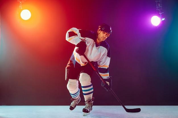 Campione. giocatore di hockey maschio sul campo da ghiaccio e sfondo colorato al neon scuro con torce elettriche. sportivo in attrezzatura, pratica del casco. concetto di sport, stile di vita sano, movimento, benessere, azione.