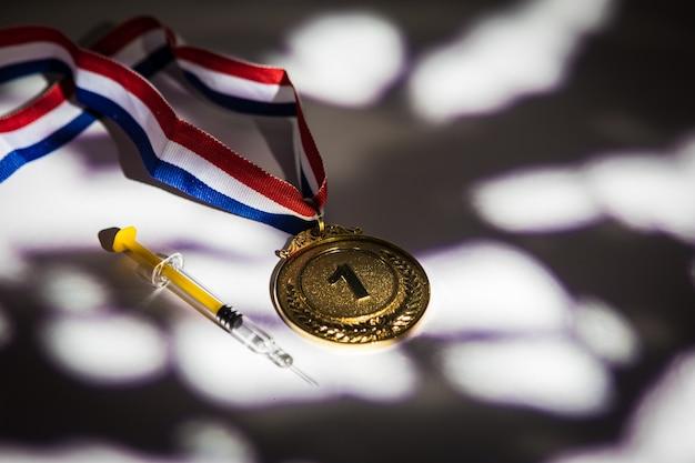Medaglia d'oro del campione e siringa con sostanza dopante con luci e ombre che entrano dalla finestra. sport e concetto di doping