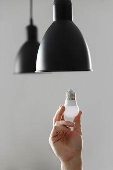 Sostituzione della lampadina per lampadina a led in lampada da terra di colore nero.