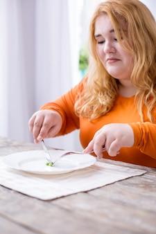 Cambiare stile di vita. triste donna sovrappeso seduta al tavolo e mangiare i piselli