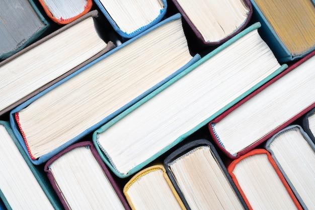 Pila caotica di libri con copertina rigida su scaffale vista in primo piano di libri con copertina rigida vintage come sfondo