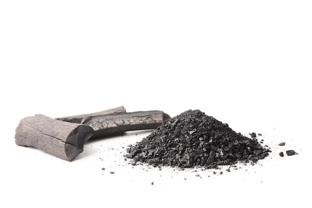Carbone di legna e polvere (carbone attivo) su fondo bianco.
