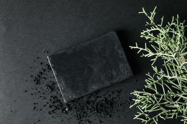 Sapone al carbone e rami di thuja su sfondo nero