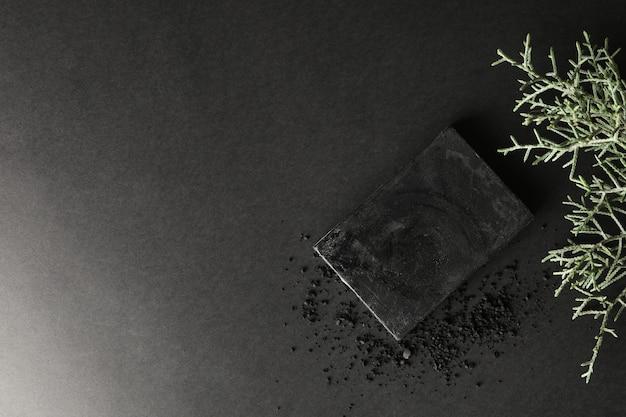 Sapone al carbone e rami di thuja sulla superficie nera