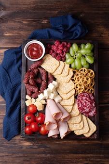 Tagliere di salumi con salsiccia, cracker, frutta e formaggio su uno sfondo di legno scuro, primo piano.