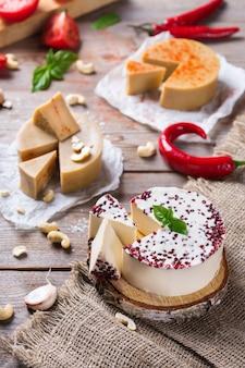 Piatto di salumi servito con formaggio crudo fermentato biologico non caseario di anacardi con snack, frutta. vegano, vegetariano, cibo a base vegetale, nutrizione e dieta, concetto di alimentazione sana.