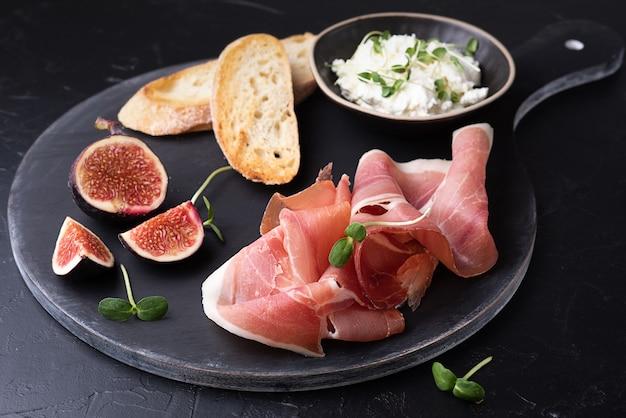 Piatto di salumi con prosciutto, formaggio, fette di pane e fichi su sfondo nero, primo piano.