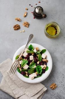 Insalata di bietole, rucola, barbabietola, ricotta e noci con olio d'oliva in un vecchio piatto di ceramica su una superficie in pietra grigia o cemento invecchiato