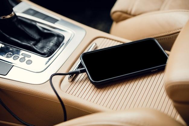 Telefono con spina del caricatore sull'auto. telefono con presa di corrente in auto