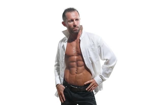 Uomo atletico carismatico in una camicia bianca sbottonata isolata su fondo bianco.