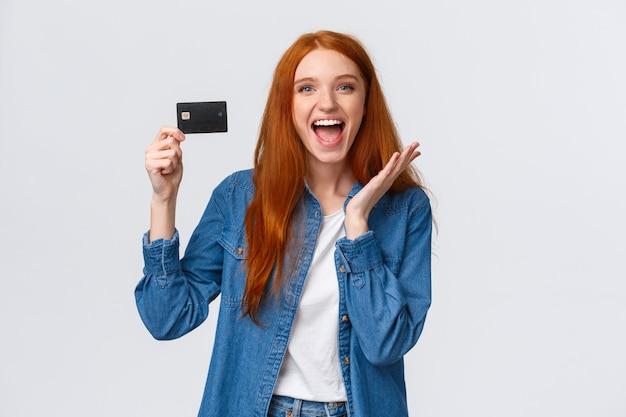 Carismatica felice studentessa rossa di bell'aspetto in abiti casual, in possesso di carta di credito con un sorriso raggiante sul viso, stupita e compiaciuta, riceve uno stipendio, come le offerte bancarie,