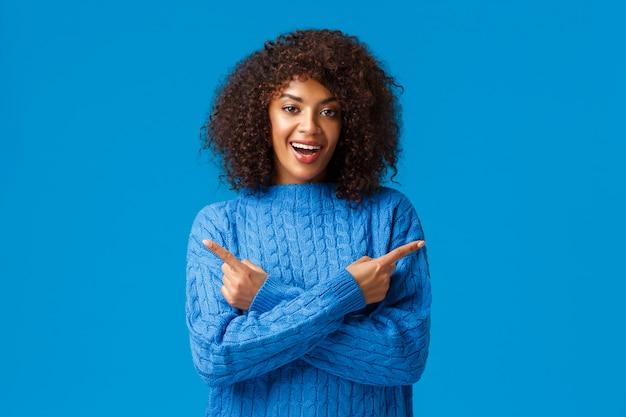 Carismatica sorridente felice donna afro-americana con taglio di capelli afro, puntando le dita a sinistra e a destra, indicando lateralmente con le mani incrociate sul petto, sorridendo, raccomandare due prodotti, pubblicità