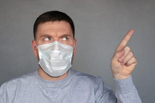 Giovane carismatico in maschera medica punta il dito indice di lato su sfondo grigio cemento
