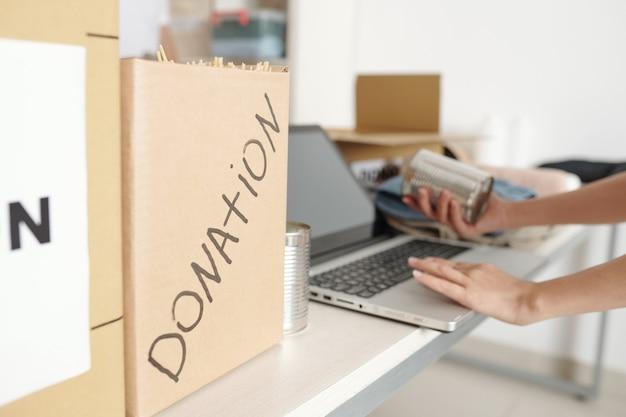 Operaio della fondazione di beneficenza che digita sul laptop quando disimballa una grande scatola con generi alimentari donati