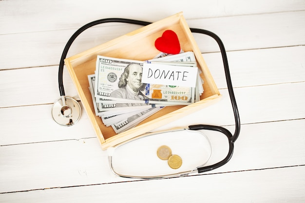 Scatola di raccolta fondi di carità con i dollari su fondo di legno bianco