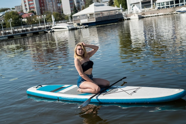 Fascino giovane donna sulla tavola da paddle supal lago della città, vacanza in estate