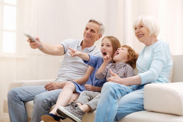 Affascinanti nonni entusiasti attivi che si godono la compagnia dei bambini seduti su un divano e guardano cartoni animati