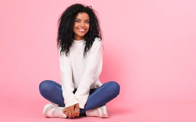 Affascinante signora afroamericana in maglione bianco lavorato a maglia e jeans blu è seduta sulla gamba sinistra mentre tiene il ginocchio destro tra le braccia e sorride sinceramente