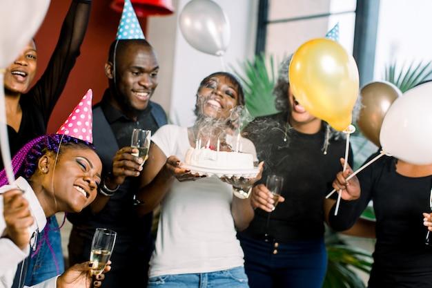 Affascinante femmina africana che soffia sulle candele sulla torta di compleanno dopo aver espresso il suo desiderio alla festa
