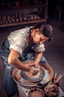 Affascinante donna artigiana crea una nuova ceramica dall'argilla su un tornio da vasaio.