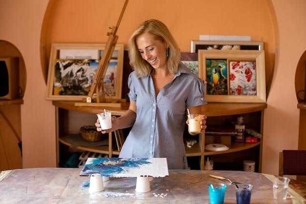 L'affascinante artista con piacere inizia a lavorare alla creazione di immagini nel suo studio d'arte. pittura per interni. hobby e artigianato. felicità e creatività. corso di pittura online. stile di vita.