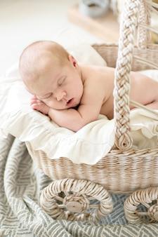 Bambino affascinante, dorme nel passeggino di vimini, crema