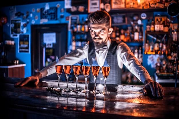Affascinante barman pone gli ultimi ritocchi su un drink al bancone del bar