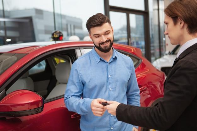 Affascinante uomo barbuto che riceve le chiavi della macchina dal venditore dopo aver acquistato una nuova automobile
