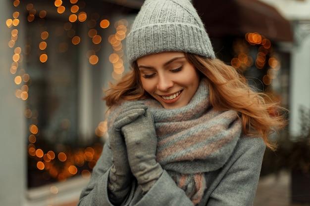 Affascinante bella donna felice con un sorriso magico in un cappotto grigio alla moda e un cappello alla moda lavorato a maglia con una sciarpa sulla strada vicino alle luci gialle in vacanza