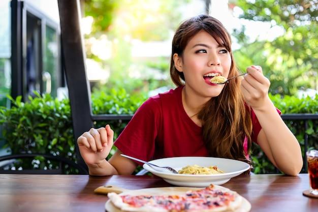 Affascinante bella donna sta godendo il suo pasto italiano in un ristorante.