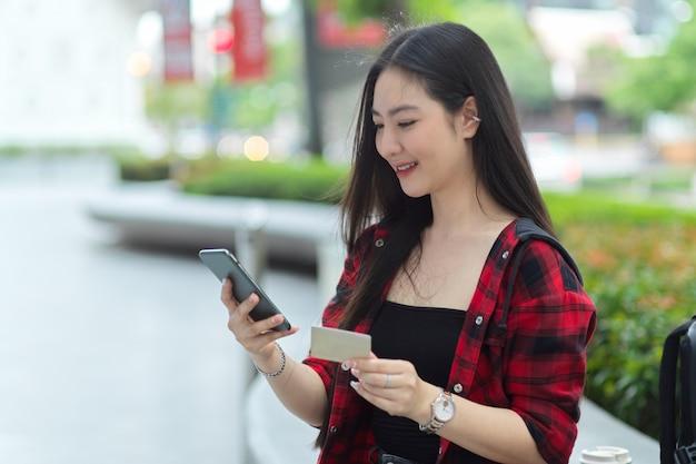 Affascinante bella donna che utilizza il telefono cellulare e la carta di credito per trasferire denaro tramite cellulare