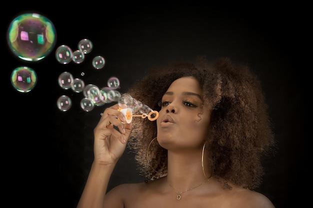 Affascinante donna nera che soffia bolle di sapone in studio