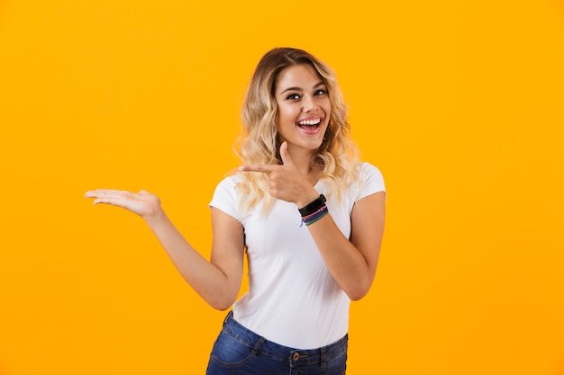 Affascinante donna bionda in abiti di base sorridendo e puntando il dito contro il copyspace sul palmo, isolato sopra la parete gialla