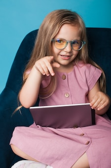 Affascinante ragazza bionda è in possesso di un tablet e punta alla telecamera su una parete blu dello studio