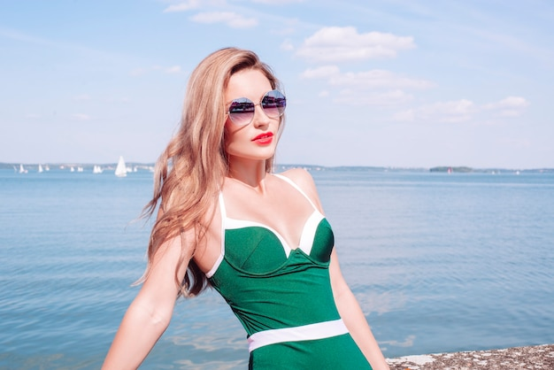 Affascinante bionda in costume da bagno verde posa sulla spiaggia di un hotel di lusso. il concetto di viaggio, turismo, ricreazione. tecnica mista