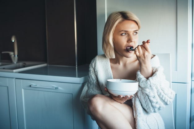 Affascinante donna bionda che mangia cereali in cucina sul pavimento mentre guarda da qualche parte