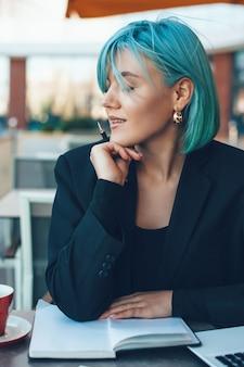 Affascinante donna dai capelli blu in posa in una caffetteria mentre scrive alcune idee su un taccuino