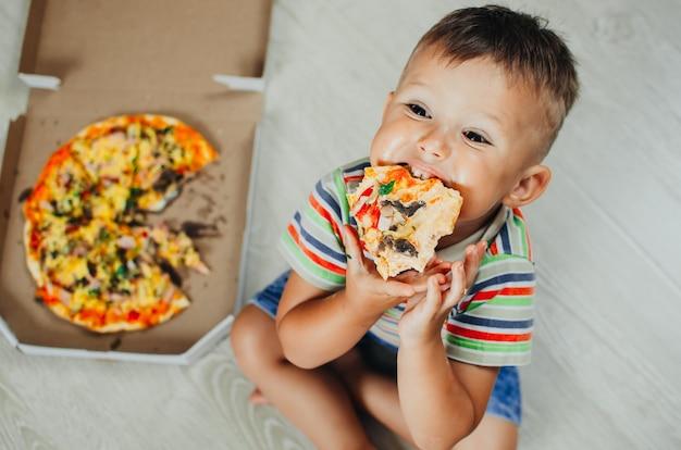 Affascinante ragazzo seduto sul pavimento che mangia pizza vista dall'alto