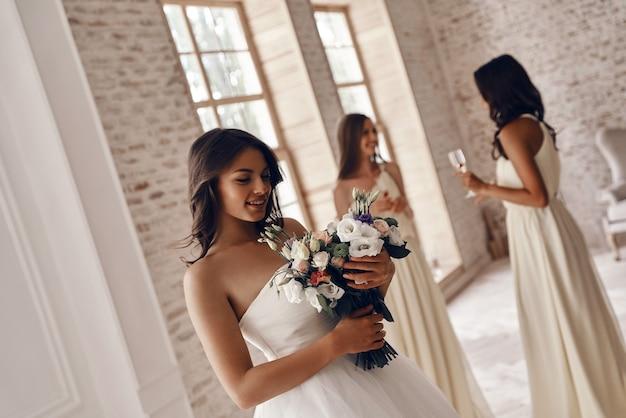 Sposa affascinante. attraente giovane donna con in mano un bouquet da sposa e sorridente mentre le sue amiche bevono champagne sullo sfondo