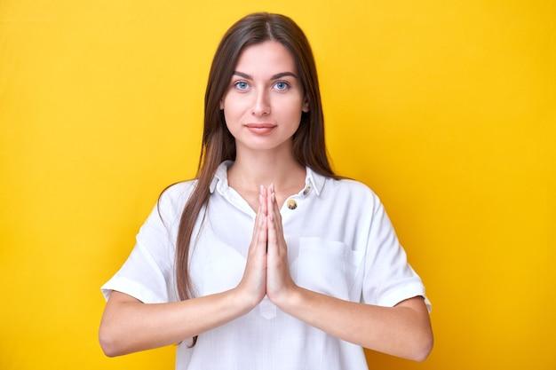 Affascinante ragazza bruna ha piegato le mani nella posa di preghiera del ringraziamento isolata su sfondo giallo