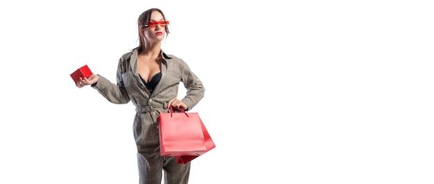 Affascinante bruna con gli occhiali in posa in studio con borse rosse e una scatola per gioielli