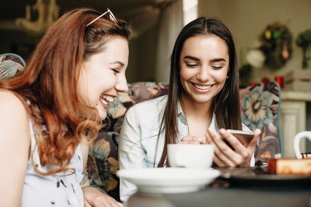 Affascinante bruna che mostra qualcosa alla sua fidanzata plus size su uno smartphone mentre ride in un caffè.